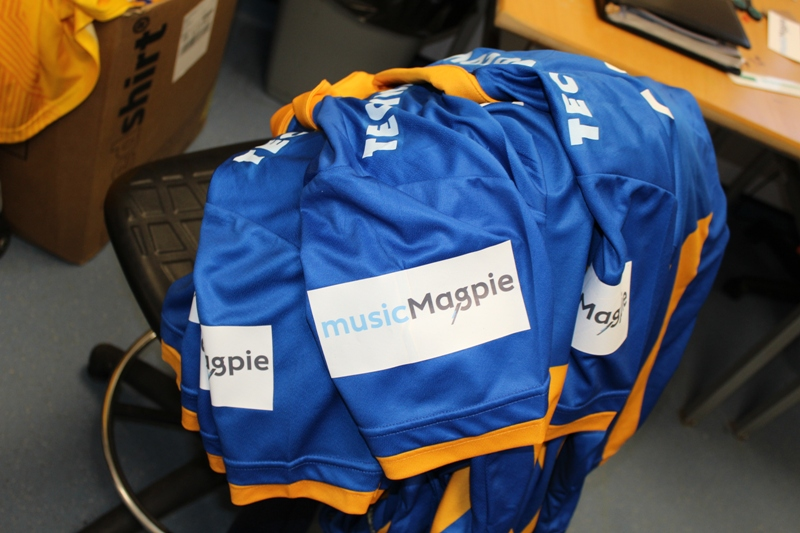 The musicMagpie logo on the sleeves of the Shrewsbury Town home shirt.